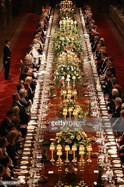 Guests listen during a speech by Britain's Queen Elizabeth II in honour of the President of Ireland Michael D Higgins at the State Banquet during the...
