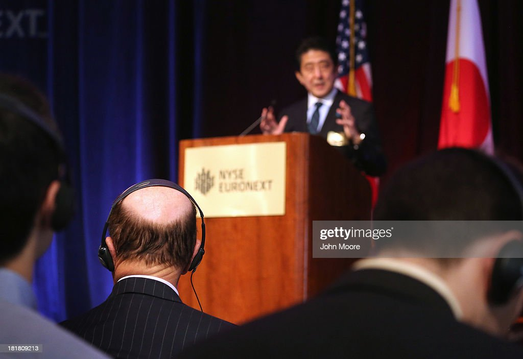 Guests listen to an English translation as Japanese Prime Minister <a gi-track='captionPersonalityLinkClicked' href=/galleries/search?phrase=Shinzo+Abe&family=editorial&specificpeople=559017 ng-click='$event.stopPropagation()'>Shinzo Abe</a> gives a speech at the New York Stock Exchange before ringing the closing bell on September 25, 2013 in New York City. Abe spoke on 'Abenomics' and Japan's economic recovery.