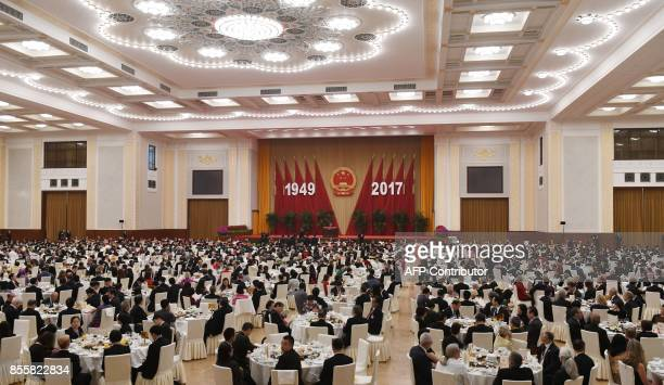 Guests listen to Premier Li Keqiang's speech at a reception on the eve of China's National Day which marks the 68th anniversary of the founding of...
