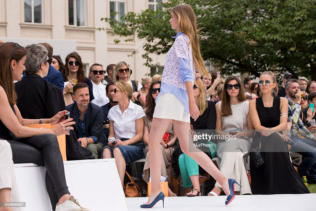 Guests look at a model as she walks the runway at the Marina Hoermanseder show during the Mercedes-Benz Fashion Week Berlin Spring/Summer 2017 at Kronprinzenpalais in Berlin, Germany on June 30, 2016.