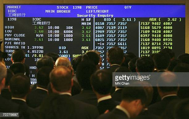 Guests look at the electronic billboard showing the Industrial and Commercial Bank Of China's stock price after the ceremony to mark their Initial...