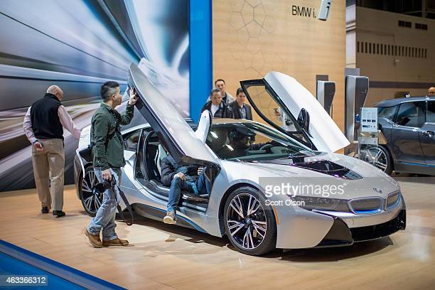 Guests look over the BMW i8 plugin hybrid sports car at the Chicago Auto Show during the media preview on February 13 2015 in Chicago Illinois The...