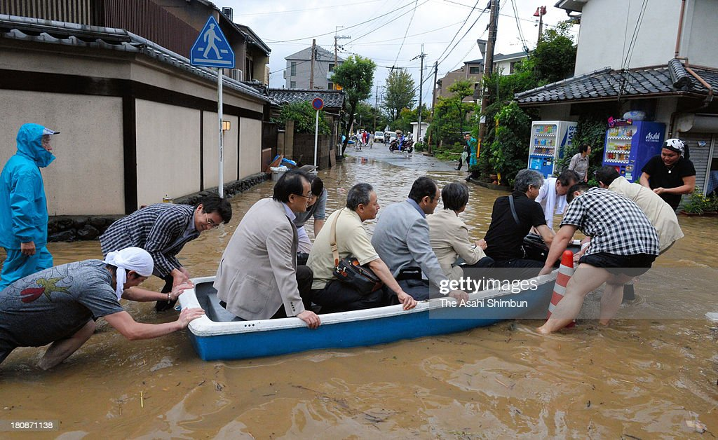 Guests of an inn flee the flooding from the Katsuragawa river triggered by typhoon Man-Yi approaching on September 16, 2013 in Ritto, Shiga, Japan. The storm hit land near Toyohashi, Aichi Prefecture, before 8 a.m. and moved along Honshu throughout the day, damaging buildings, disrupting transportation and causing blackouts, three killed and five missing.