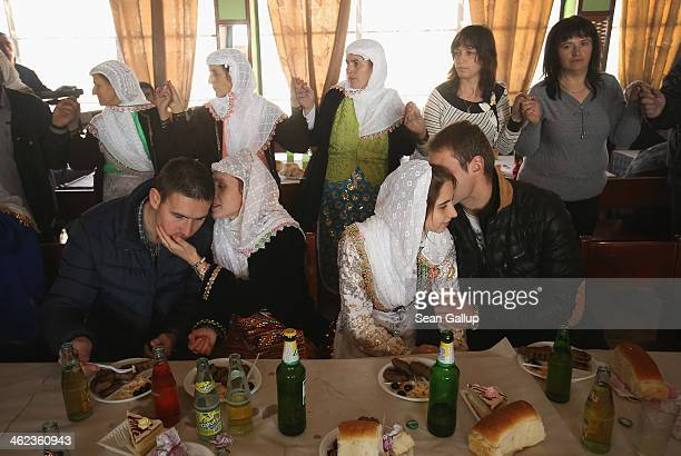 Guests of groom Mustafa Sirakov participate in a group dance as two couples chat in a restaurant on the first day of twoday wedding celebrations for...