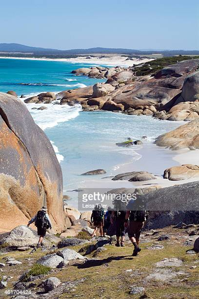 Guests on Cradle Mountain Huts' Bay of Fires walk wander down through boulders tainted orange by a native moss at the Bay of Fires Cradle Mountain...