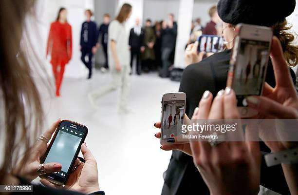 Guests photograph the Matthew Miller show using smart phones at the London Collections Men AW15 at Victoria House on January 10 2015 in London England