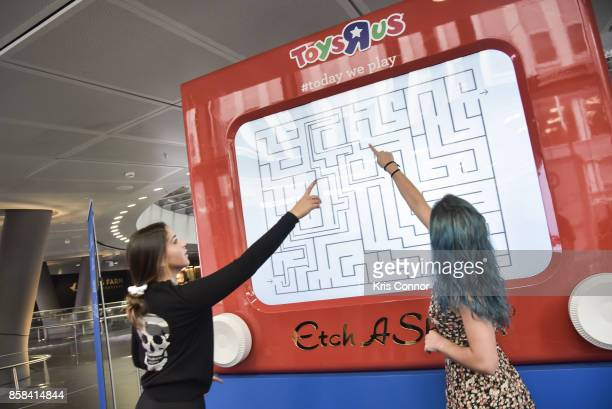 Guests play with a giant Etch A Sketch during the 'Toys 'R' Us Takes Over Fulton Street Subway Station with Giant Etch A Sketch' event at Fulton...