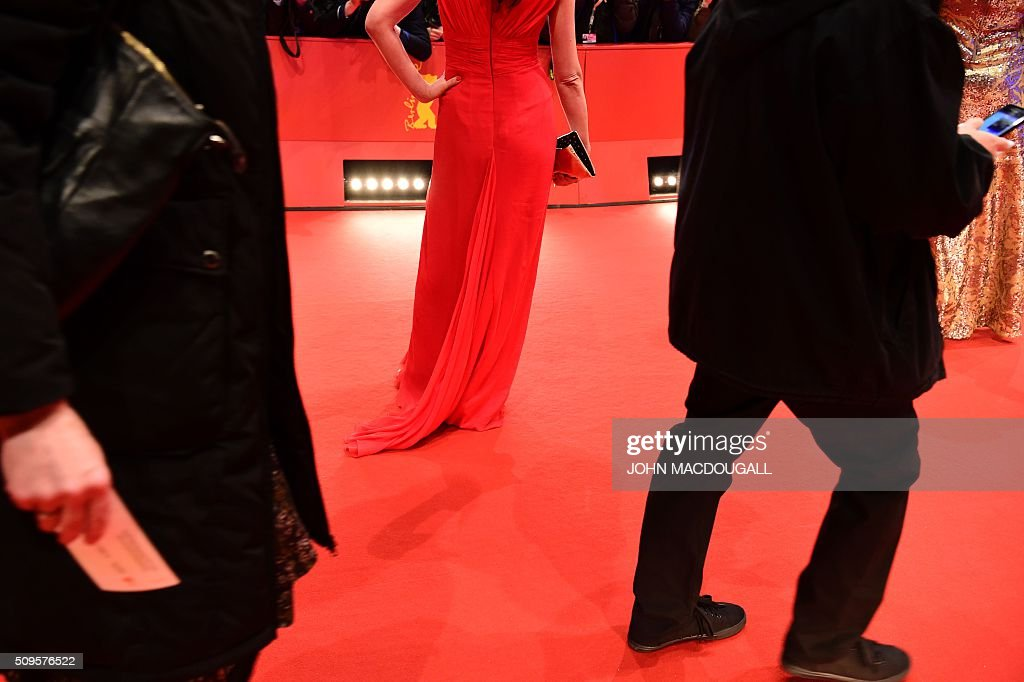 Guests pose for photographers as they arrive on the red carpet for the film 'Hail, Caesar!' screening as opening film of the 66th Berlinale Film Festival in Berlin on February 11, 2016. Eighteen pictures will vie for the Golden Bear top prize at the event which runs from February 11 to 21, 2016. / AFP / John MACDOUGALL