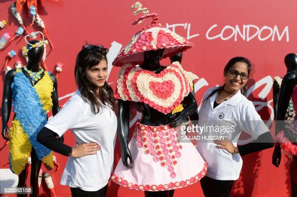 Guests pose with a mannequin wearing a dress decorated with condoms during an event to mark International Condom Day in New Delhi on February 13 2017...