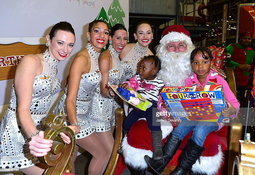 Guests pose with Santa and the Radio City Rockettes at the 3rd Annual Garden of Dreams Foundation & Delta Air Lines' 'Holiday in the Hangar' event at John F. Kennedy International Airport on December 11, 2012 in New York City.