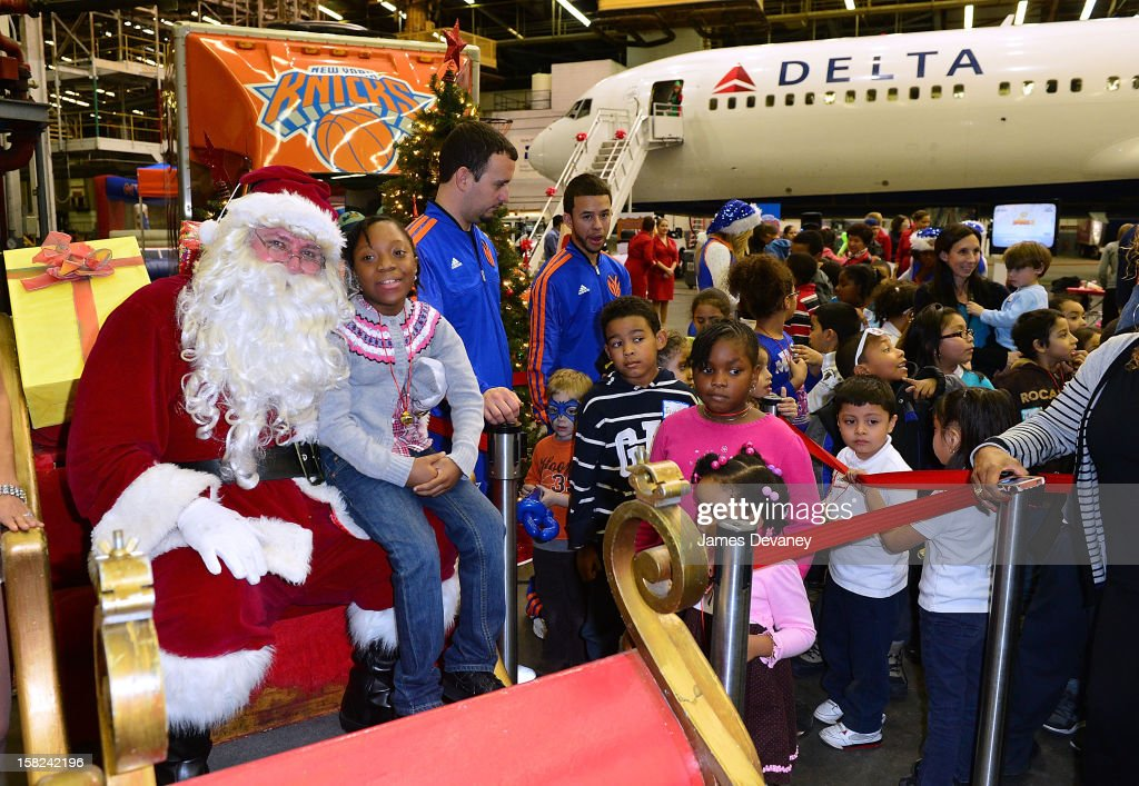 Guests pose with Santa at the 3rd Annual Garden of Dreams Foundation & Delta Air Lines' 'Holiday in the Hangar' event at John F. Kennedy International Airport on December 11, 2012 in New York City.