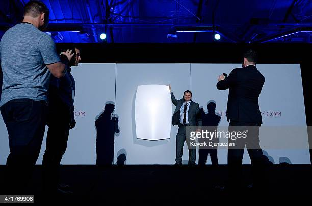 Guests pose with the Powerwall unit after Elon Musk CEO of Tesla unveiled suit of batteries for homes businesses and utilities at Tesla Design Studio...