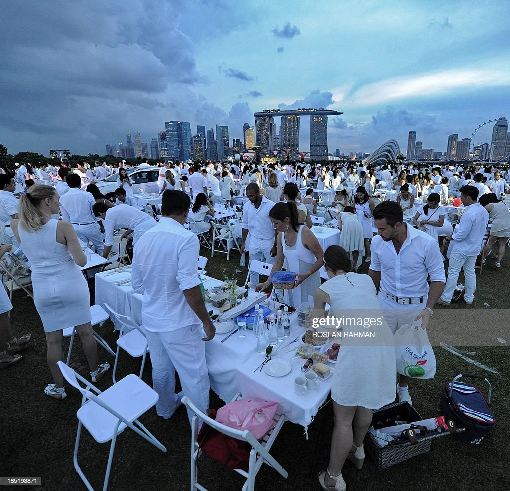 Guests prepare tables at Marina Barrage during the annual Diner en Blanc, the worlds only viral culinary event, a chic secret pop-up style picnic imported from France, in Singapore on October 18, 2013. More than 2,400 guests turned up to participate in Singapores second edition of Dîner en Blanc.