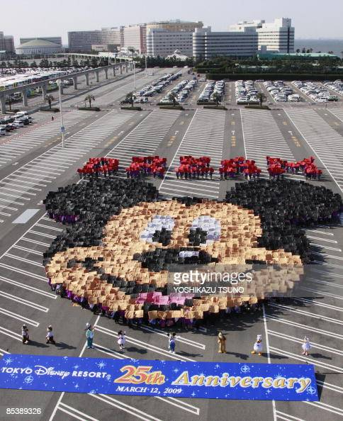 2500 guests raise color boards to form the face of Mickey Mouse for the 25th anniversary of the Tokyo Disneyland at the park's parking lot at Urayasu...