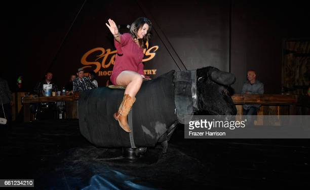 Guests ride a mechanical bull during ACM After Party For A Cause at Stoney's Rockin' Country on March 30 2017 in Las Vegas Nevada