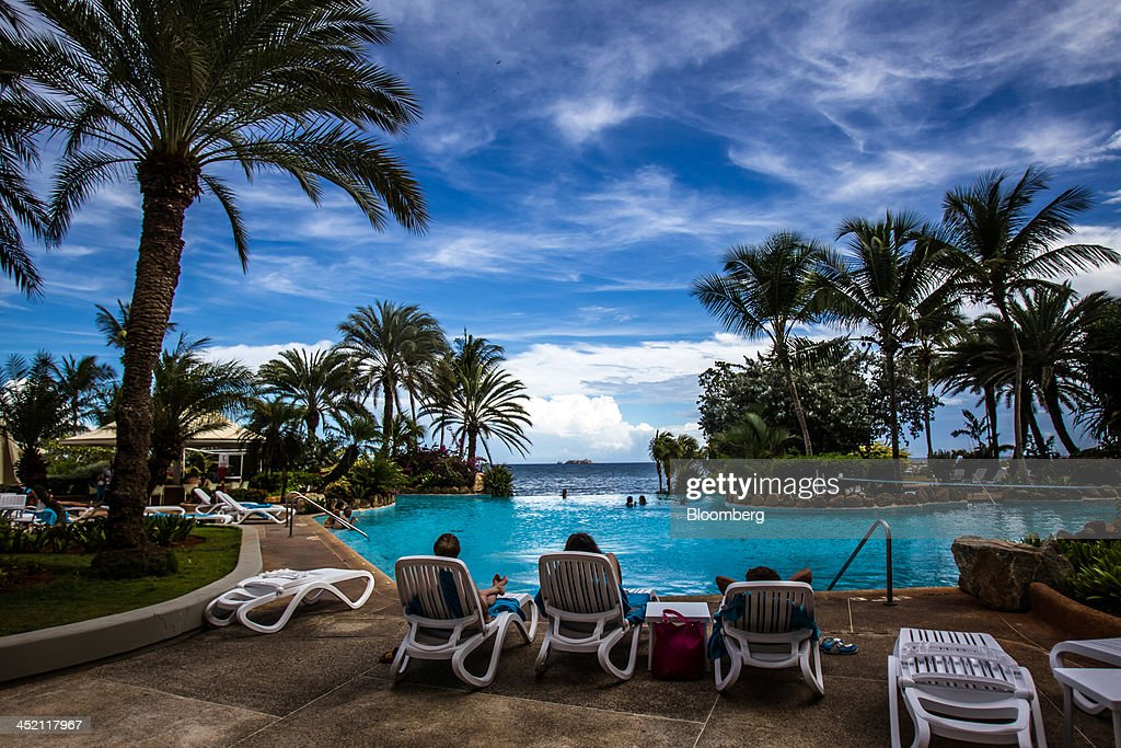 Guests sit by the pool at the state-run Venetur Hotel, the site of the first Russia-Venezuela Oil Congress, on Margarita Island in Nueva Esparta, Venezuela, on Thursday, Nov. 21, 2013. OAO Rosneft, Russia's largest oil producer, plans to invest $13 billion in five projects in Venezuela over five years and buy at least part of OAO Lukoil's stake in a producing field in the South American nation. Photographer: Meridith Kohut/Bloomberg via Getty Images