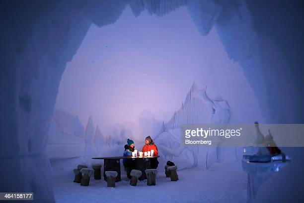 Guests sit illuminated by candle in the lobby of the igloo hotel operated by IgluDorf GmbH on the Parsenn mountain in this arranged photograph taken...