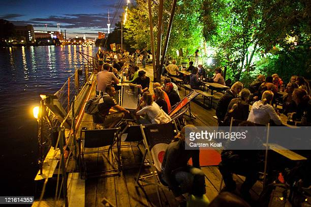 Guests sitting on the water spending the evening in the beach bar Oststrand behind the East Side Galery on August 20 2011 in Berlin Germany Berlin...
