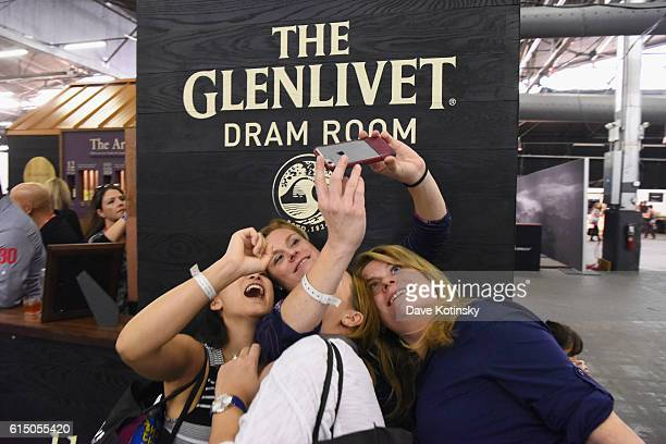 Guests take a selfie in front of the Glenlivet Dram Room booth during the Grand Tasting presented by ShopRite featuring Samsung culinary...