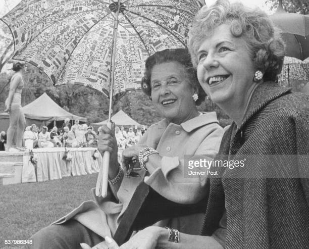 Guests Take Cover From Rain At Goodwill Garden Gala Sharing an umbrella are Mrs Ellen Brown Gould left and Mrs William Glass who watch fashion show...