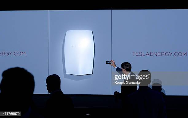 Guests take photographs of the Powerwall system after Elon Musk CEO of Tesla unveiled suit of batteries for homes businesses and utilities at Tesla...