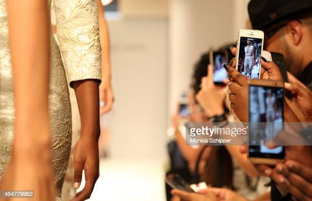 Guests take photos as a model walks the runway at the Amir Taghi fashion show during MercedesBenz Fashion Week Spring 2015 at the Helen Mills Event...