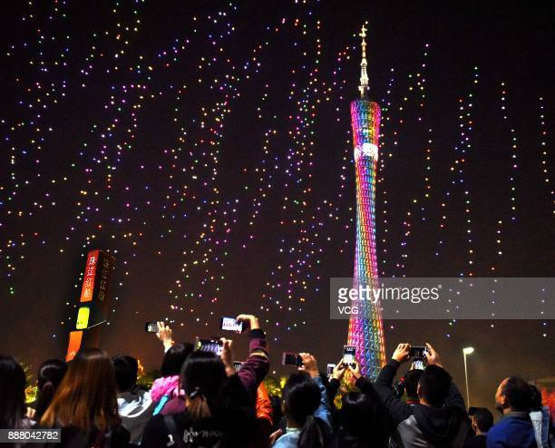 Guests take photos of over 1000 UAVs flying in formation during a welcoming banquet around Canton Tower on day two of the 2017 Fortune Global Forum...