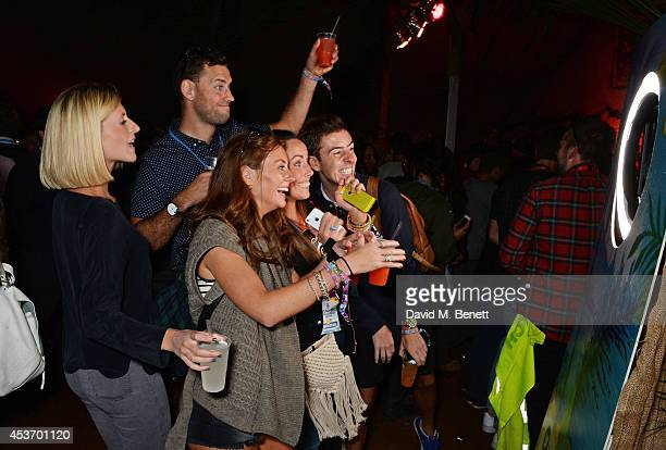 Guests take selfies at the Mahiki Rum Bar for the launch of the Mahiki Rum Family backstage during day 1 of the V Festival 2014 at Hylands Park on...