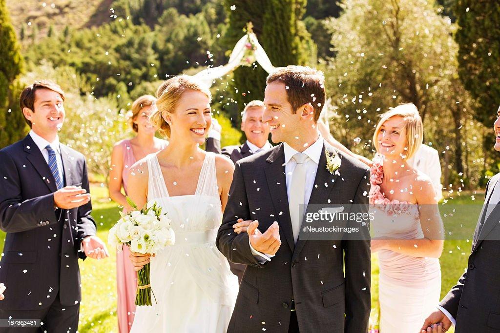 Gli ospiti lanciare Coriandoli e stelle filanti su coppia nel giardino matrimonio : Foto stock