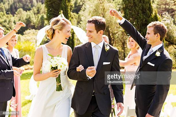 Guests Throwing Confetti On Couple During Outdoor Wedding