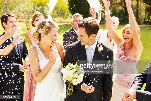 Guests Throwing Confetti On Couple During Wedding Reception