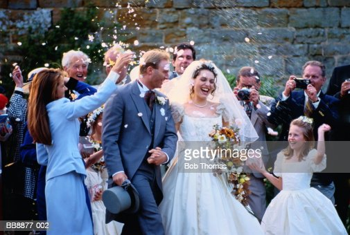 Guests throwing confetti over bride and groom as they leave church