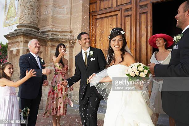 Guests throwing confetti over bride and groom, bride smiling, portrait