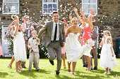 Guests Throwing Confetti Over Bride And Groom As They Run Towards Camera