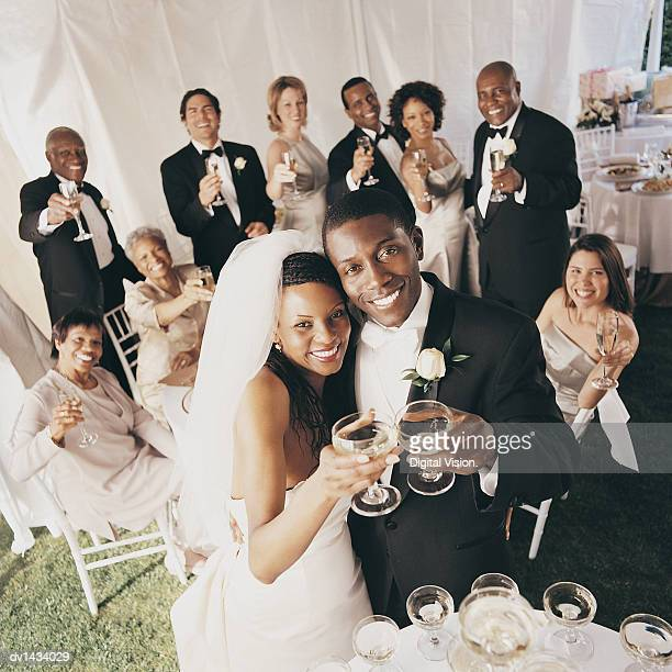 Guests Toast the Bride and Groom at a Wedding Reception in a Marquee