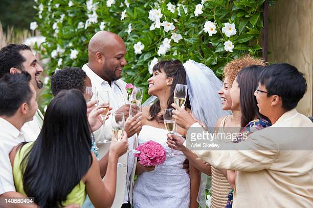 Guests toasting bride and groom on wedding day