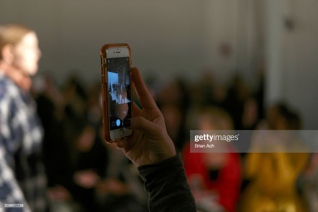Guests use camera phones to photograph models walking the runway at the Marissa Webb Fall 2016 fashion show during New York Fashion Week: The Shows at The Gallery, Skylight at Clarkson Square on February 11, 2016 in New York City.