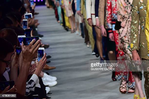 Guests use their mobile phones to record the end of the show for fashion house Gucci at the Men SpringSummer 2016 Milan's Fashion Week on June 22...