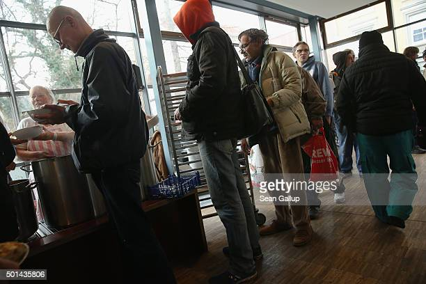 Guests wait in line for a hearty lunch at the soup kitchen at the Franciscan monastery in Pankow district on December 15 2015 in Berlin Germany The...
