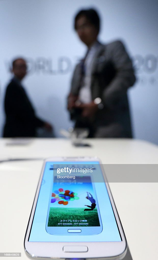 Guests walk behind a Samsung Electronics Co. Galaxy S4 smartphone for NTT DoCoMo Inc. displayed during the Galaxy S4 World Tour 2013 Tokyo event in Tokyo, Japan, on Thursday, May 16, 2013. Samsung Electronics reported a record quarterly profit in April for the three months ended March 31. Photographer: Tomohiro Ohsumi/Bloomberg via Getty Images