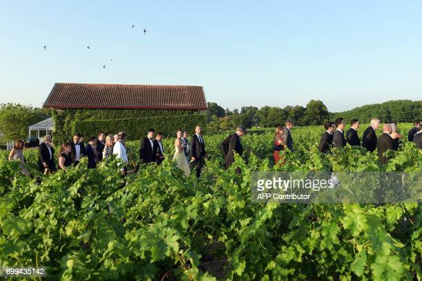 CORRECTION Guests walk in the vineyards during the 65th 'Fete de la Fleur' at Chateau MalarticLagraviere in Leognan southwestern France on June 21...