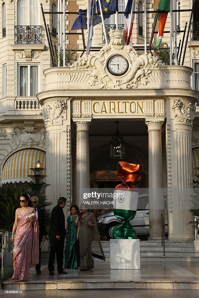 Guests walk outside the Carlton Hotel in the southeastern French city of Cannes on October 14, 2013 during the wedding party of a London-based Indian couple. The Carlton palace was entirely booked for several nights to accomodate guests for the wedding of Grover and Ria Dubash.