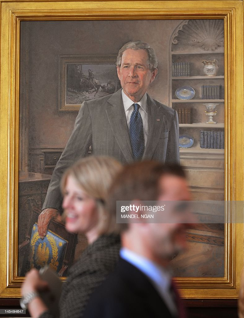 walk past a portrait fo former US president George W. Bush during its ...