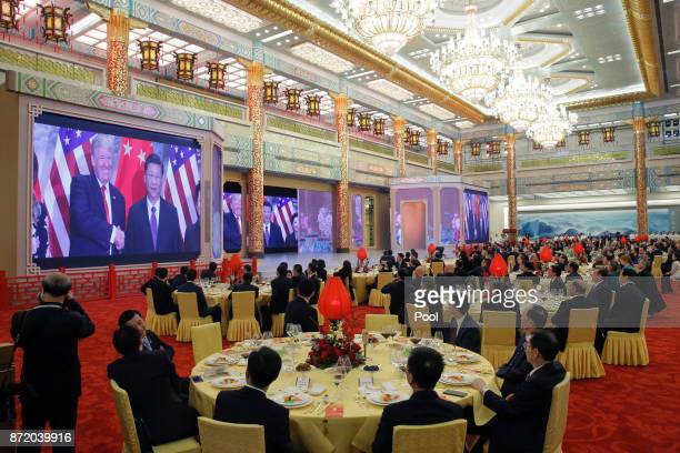Guests watch a video about meetings between US President Donald Trump and China's President Xi Jinping at a state dinner at the Great Hall of the...