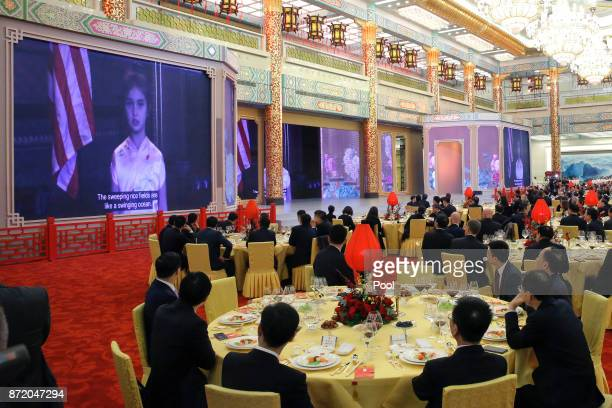 Guests watch a video of Arabella Kushner granddaughter of US President Donald Trump sing a traditional Chinese song during a state dinner at the...