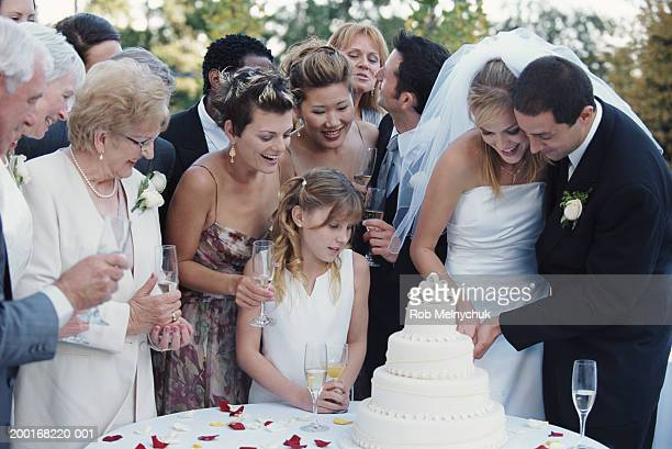 Guests watching bride and groom cut cake at wedding reception