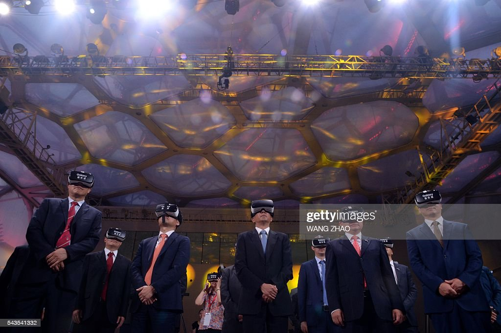 Guests wear virtual reality glasses during a ceremony to unveil the Chinese Olympic team's uniforms for the Rio 2016 Olympic Games, in Beijing on June 29, 2016. The uniforms were unveiled at a ceremony in the Water Cube, the venue for the swimming competition at the 2008 Beijing Olympic Games. / AFP / WANG