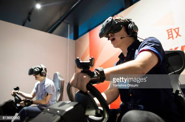 Guests wearing HTC Corp Vive virtual reality headsets try the Mario Kart Arcade GP VR attraction at the VR Zone Shinjuku theme park operated by...