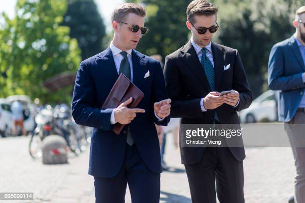 Guests wearing navy suits with white pocket square and clutch green tie is seen during Pitti Immagine Uomo 92 at Fortezza Da Basso on June 13 2017 in...