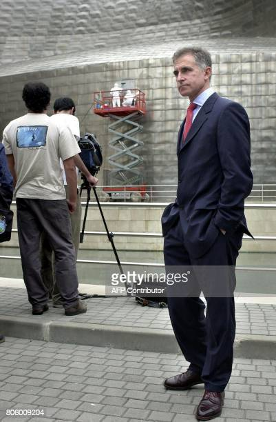 Guggenheim Museum director Juan Ignacio Vidarte poses 13 June 2001 as titanium panels covering the building in Bilbao are being cleaned Several...